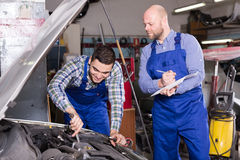 Mechanic calculating  price of work Stock Image