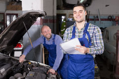 Mechanic calculating the price of work Royalty Free Stock Images