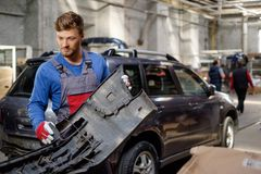 Mechanic with car bumper Royalty Free Stock Image