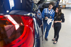 Mechanic in car garage with customer. Mechanic explains the car repairs to the customer in his garage royalty free stock photography
