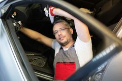 Mechanic in a car interior Royalty Free Stock Image