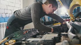 Mechanic in car repairing service - diagnostics in engine compartment. Close up royalty free stock images