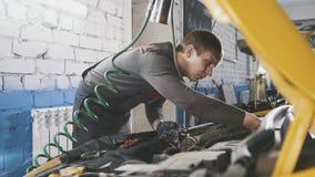 Mechanic in car repairing service - diagnostics in engine compartment. Close up stock photos