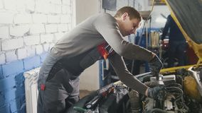Mechanic in car repairing service - diagnostics in engine compartment. Close up stock image