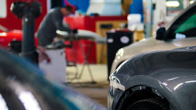 Mechanic in car service fixing and repairing detail of automobile, defocused background Royalty Free Stock Photos