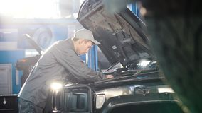 Mechanic in car service - repairing in engine compartment for luxury SUV - slider shot. Wide angle stock footage