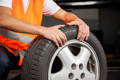 Mechanic With Car Tire At Garage Royalty Free Stock Image