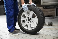 Mechanic with car tire in service center. Closeup Stock Images