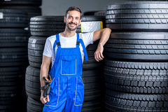 Mechanic with car tires. In tire store Royalty Free Stock Images