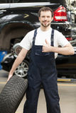 Mechanic with car wheel. Royalty Free Stock Photography
