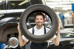 Mechanic with car wheel. Cheerful young auto mechanic looking through the car wheel and smiling stock photo