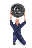 Mechanic with car wheel Royalty Free Stock Photography