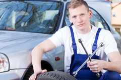 Mechanic with car wheel unscrewing key Royalty Free Stock Image