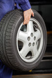 Mechanic Carrying Car Wheel At Garage Royalty Free Stock Photography