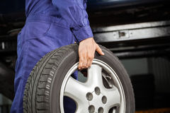 Mechanic Carrying Tire At Garage Stock Images