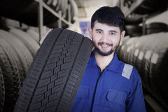 Mechanic carrying tire in the store. Middle eastern mechanic smiling at the camera while carrying a tire in the tire store Stock Photography