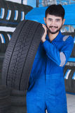 Mechanic carrying tire in the store Royalty Free Stock Images