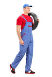 Mechanic carrying a tire and walking Stock Photo