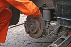 Mechanic changing brake disc. On van Stock Images