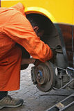 Mechanic changing brake disc. On van Stock Photos
