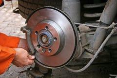 Mechanic changing brake disc. Engineer changing brake disc on van Royalty Free Stock Photos
