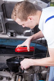 Mechanic changing car oil Stock Photography