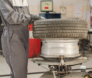 Mechanic changing car tire. Mechanic changing car tire with bead breaker tool Stock Photography