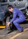 Mechanic Changing Car Tire At Repair Shop Royalty Free Stock Photo