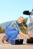 Mechanic changing a car tyre on an open road. Male mechanic changing a car tyre on an open road Royalty Free Stock Images