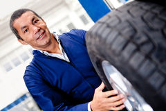 Mechanic changing car wheel Stock Images