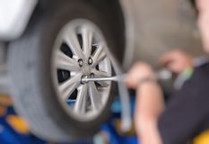 Mechanic changing car wheel in auto repair shop. serviceman wren Stock Images