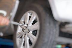 Mechanic changing car wheel in auto repair shop. serviceman wren Royalty Free Stock Image