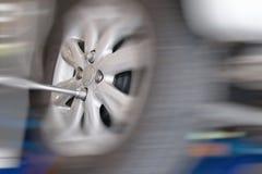 Mechanic changing car wheel in auto repair shop. serviceman wren Stock Photography