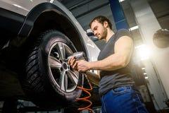 Mechanic Changing Car Wheel In Auto Repair Garage Stock Image