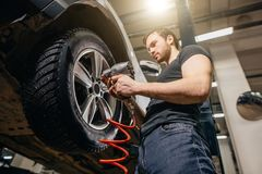 Mechanic Changing Car Wheel In Auto Repair Garage Stock Images