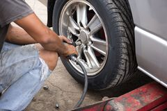Mechanic changing car wheel with  ipneumatic wrench changing car. Mechanic changing car wheel with  ipneumatic wrench in garage changing car wheel with Royalty Free Stock Photo