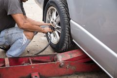 Mechanic changing car wheel with  ipneumatic wrench. In garage Royalty Free Stock Images