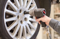 Mechanic changing car wheel. Mechanic changing car wheel at service Stock Photos