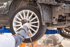 Mechanic changing car wheel. Mechanic changing car wheel at service Stock Image