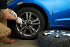 Mechanic changing damaged car wheel. Man installing car wheel Royalty Free Stock Image