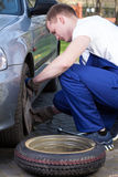 Mechanic changing flat tyre Stock Images