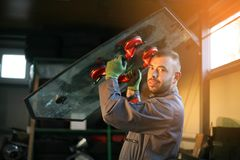 Mechanic working in auto repair shop. Mechanic changing glass workshop.Looking at camera Royalty Free Stock Photo