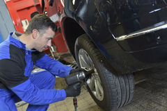 Mechanic changing a tire in car garage Royalty Free Stock Photos