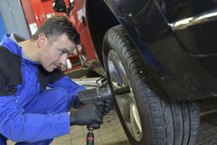 Mechanic changing tire on car stock photography