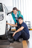 Mechanic Changing Tire With Customer At Garage. Portrait of smiling mechanic changing tire with female customer standing at garage Stock Photos