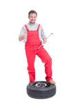 Mechanic changing tire and showing like Royalty Free Stock Image