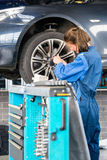 Mechanic Changing Tire From Suspended Car In Garage Royalty Free Stock Image