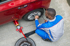 Mechanic Changing Tire With Wrench. Young African Mechanic Changing Tire Of A Car With Wrench Royalty Free Stock Photo