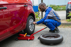 Mechanic Changing Tire With Wrench. Young African Mechanic Changing Tire Of A Red Car With Wrench Stock Photography