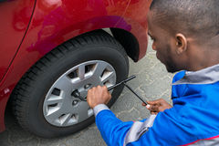 Mechanic Changing Tire With Wrench. Young African Mechanic Changing Tire Of A Red Car With Wrench Royalty Free Stock Images